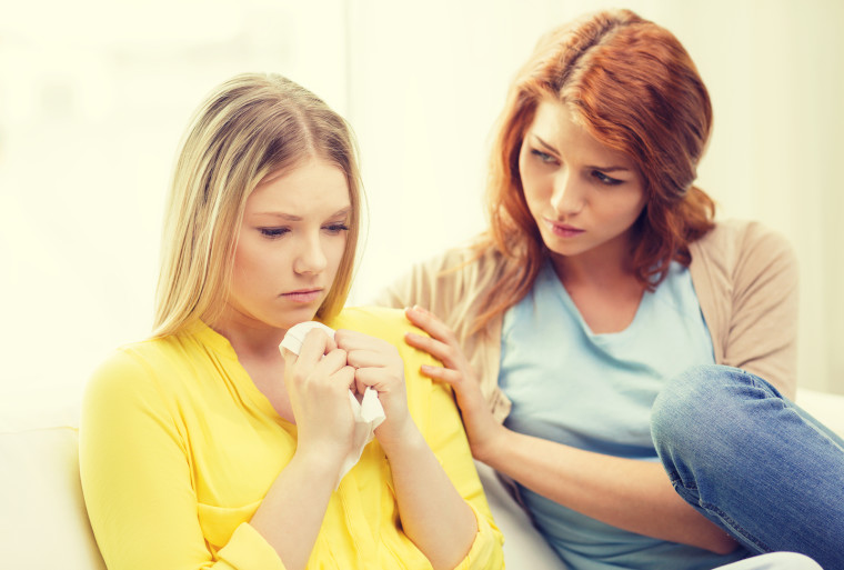 friendship and people concept - one teenage girl comforting another after break up